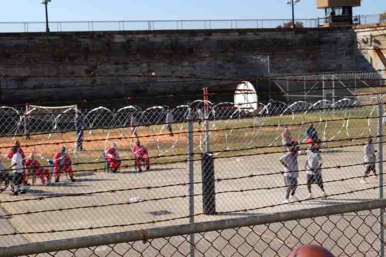 shows people behind a fence with razor wire on the top, they're in the yard of Central Prison in Raleigh
