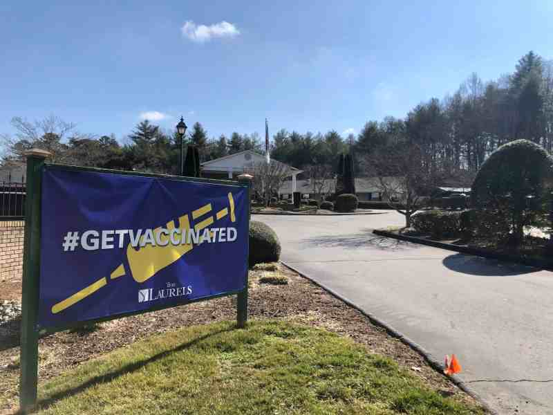 """We see a purple sign with a yellow shot and white lettering that reads, """"Hashtag Get Vaccinated,"""" in front of the Laurels of Hendersonville, an assisted living facility building with colonial white arches."""