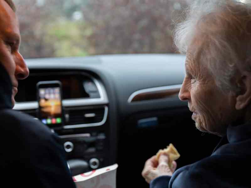 the photo is taken from the back seat of a car. You can see a man in profile leaning over to talk to his mom, also in profile