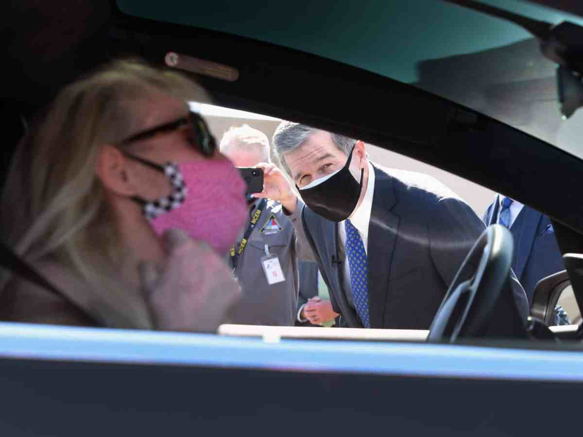 A man in a black mask bends over to peer into the cab of a vehicle where a woman in a pink mask, worn against COVID, sits.