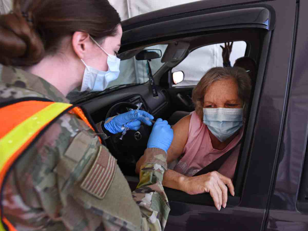 A woman in a paper surgical mask worn against COVID leans out the window of the drivers seat of her car so a woman in a mask can give an injection in her right arm.