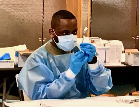 Man in blue medical gown loads COVID vaccine into a syringe