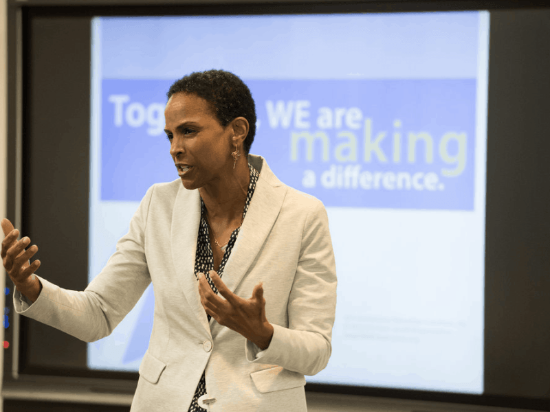 photo shows a Black woman in a white suit giving a talk in front of a screen that says 'Together we are making a difference'