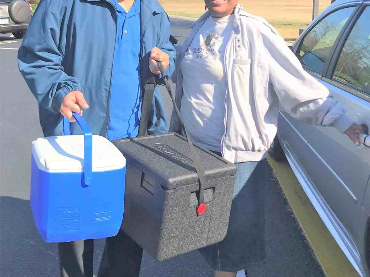 image shows two people smiling and holding coolers full of meals for seniors