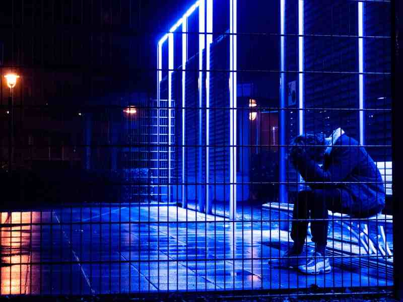 a person sits with their head in their hands behind bars, backlit by blue lights