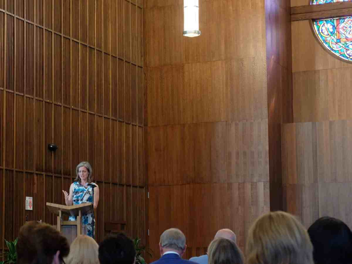 Shows a woman speaking to a crowd of people sitting in a wood paneled chapel. Behind her is a rose window.