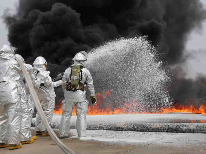 shows men in reflective suits with respirators on their backs putting out a fire with large jets of white PFAS foam