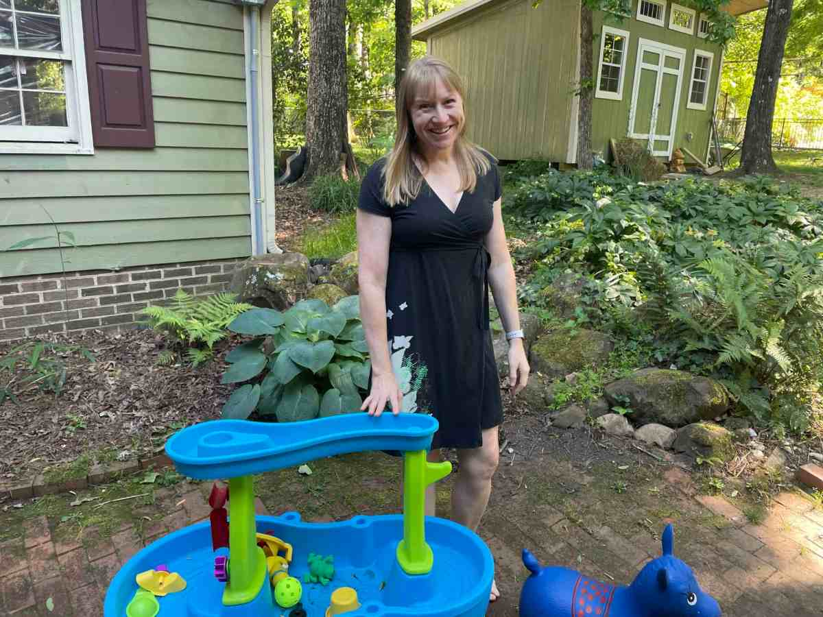 Woman who is a foster mom standing next to a plastic play table in her backyard.