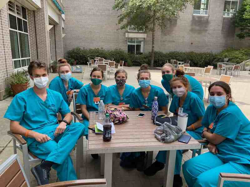 8 students in scrubs and masks lean in around a picnic table