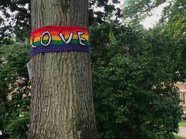 """shows a large oak trunk surrounded by a crocheted rainbow scarf with the word """"LOVE"""" embroidered in black and white on top."""