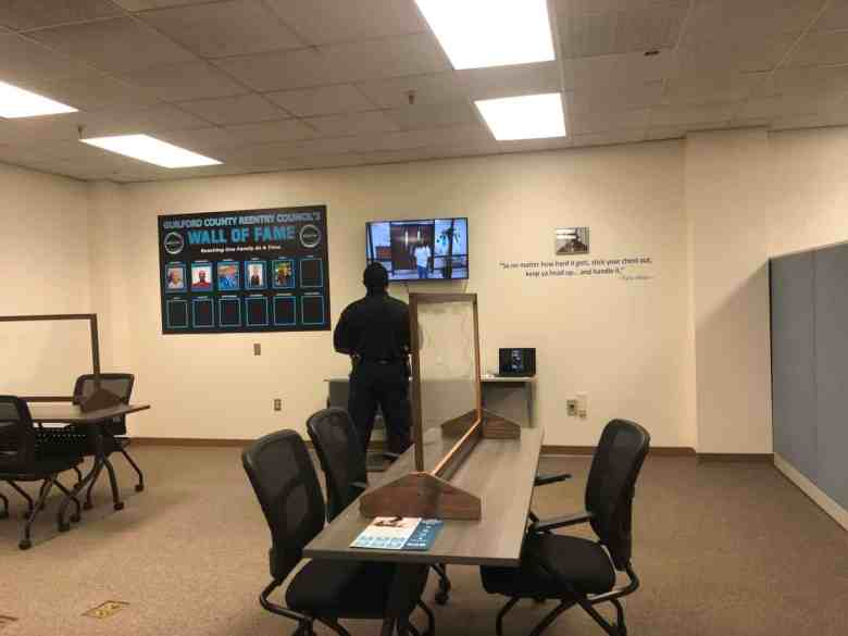 """A man watches a TV behind conference tables and chairs. The Guilford County Reentry Council's """"Wall of Fame"""" is to his left. To his right is a Tupac Shakur quote: """"So no matter how hard it gets, stick your chest out, keep ya head up... and handle it."""""""
