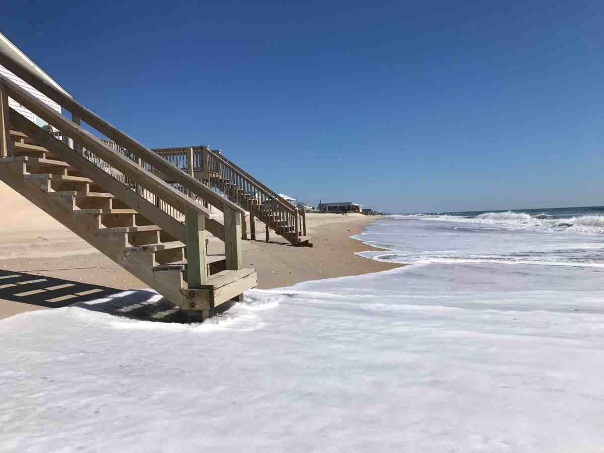 shows waves licking the bottom of steps leading up to a beach house that is now threatened by climate change warmed waters