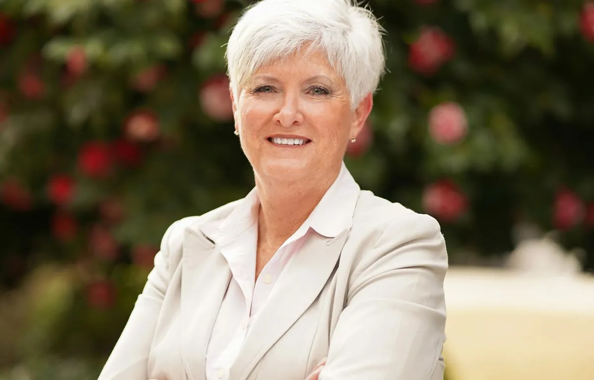 An older white woman with silver hair wearing a tan suit smiles at the camera