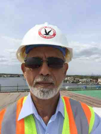 A selfie taken by Muhammad Siddiqui at work wearing a protective helmet and a neon vest and sunglasses
