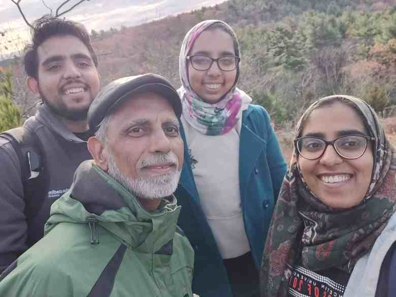 The Siddiqui family on a hike with different colored trees surrounding