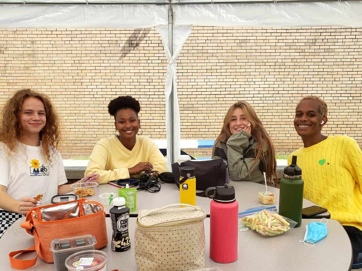 shows four young people wearing yellow to signify suicide awareness sitting around an outdoor table. They're looking at the camera and smiling.