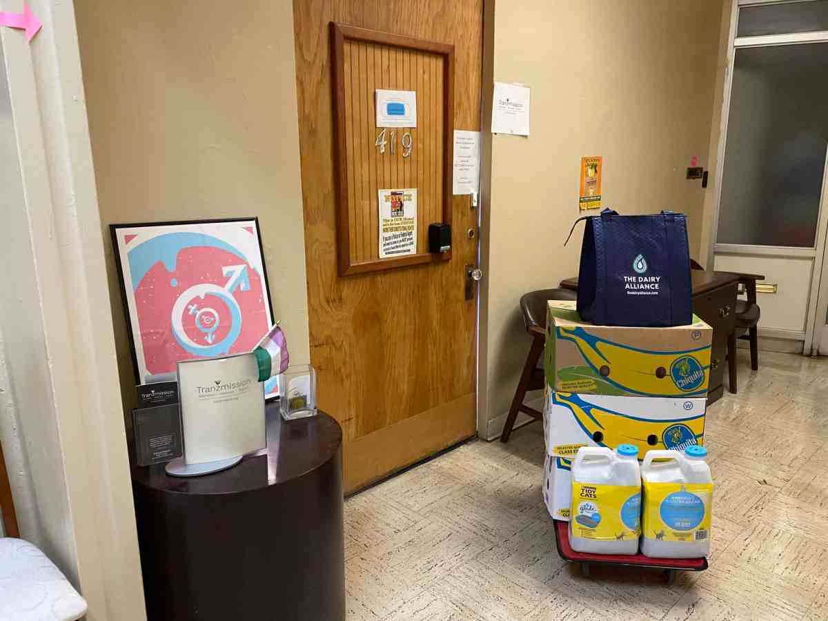 In front of a wooden office door we see a table with a pamplet labeled Transmission and poster of the transgender symbol and a genderqueer pride flag. We see some boxes with bananas on them and cat litter.