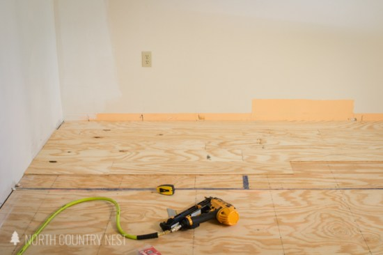 using an air gun to install plywood flooring