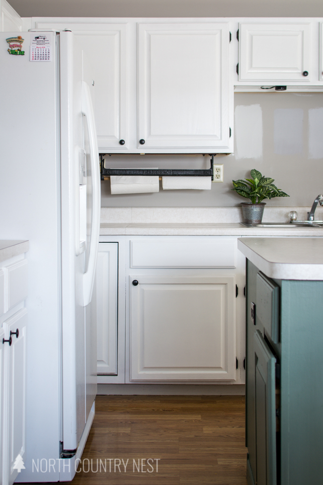 white kitchen cabinets and green island