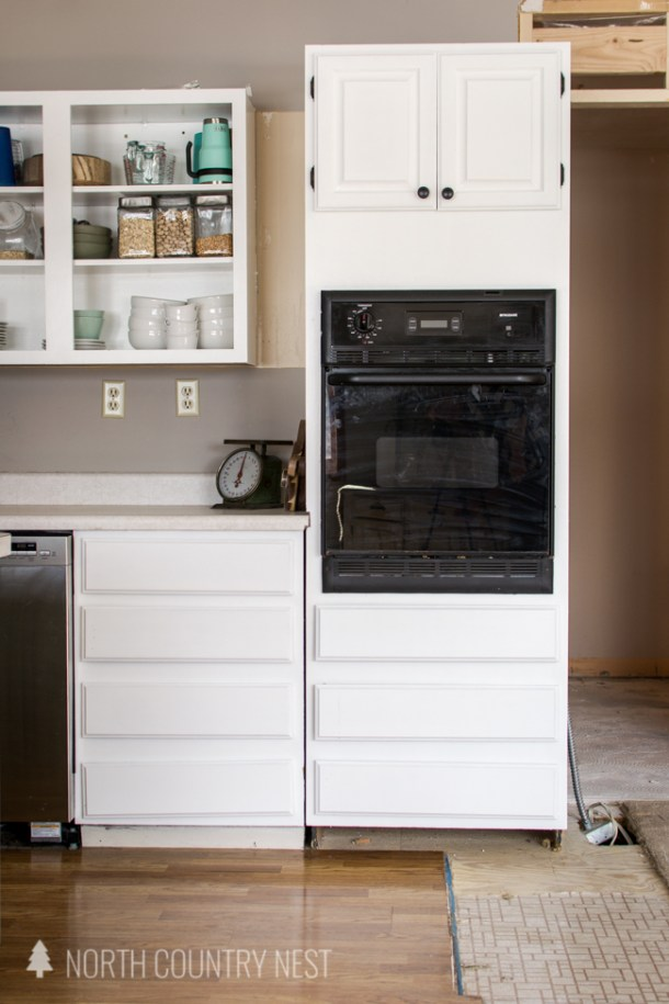 white kitchen cabinets with black oven