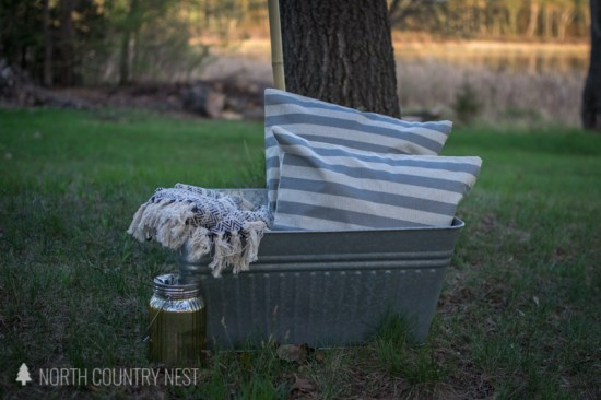 galvanized bucket outside with throw pillows and summer blanket