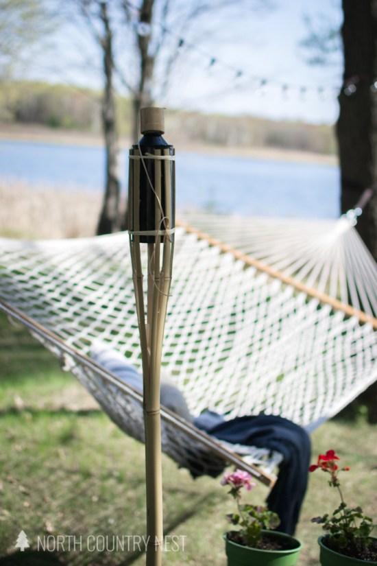 outdoor tiki torch next to hammock