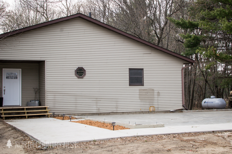 side of the house with foundation poured for garage
