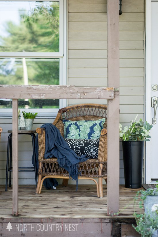 wicker chair with patterned pillows and blue throw