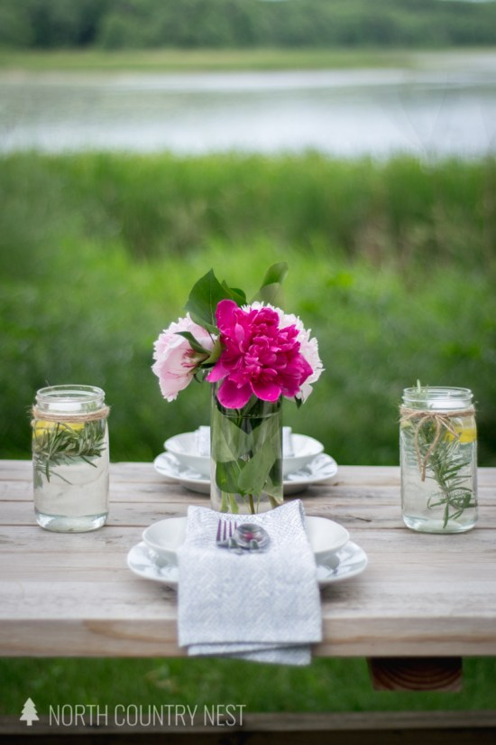 pink peonies on wooden farmhouse table with white dishes