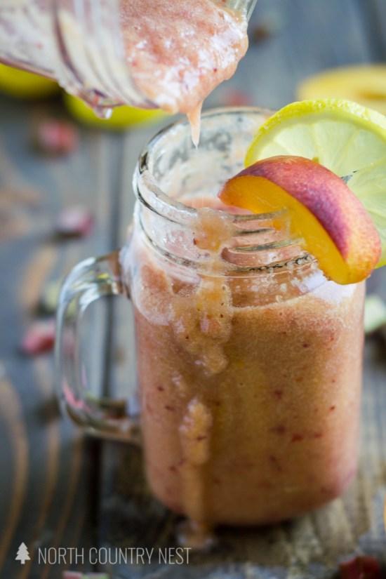 pouring peach rhubarb smoothie into mason jar glass