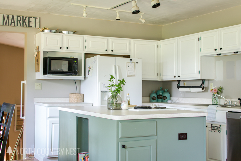 green kitchen island and white cabinets