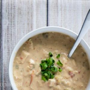 white bean chili soup in white bowl on wood backdrop