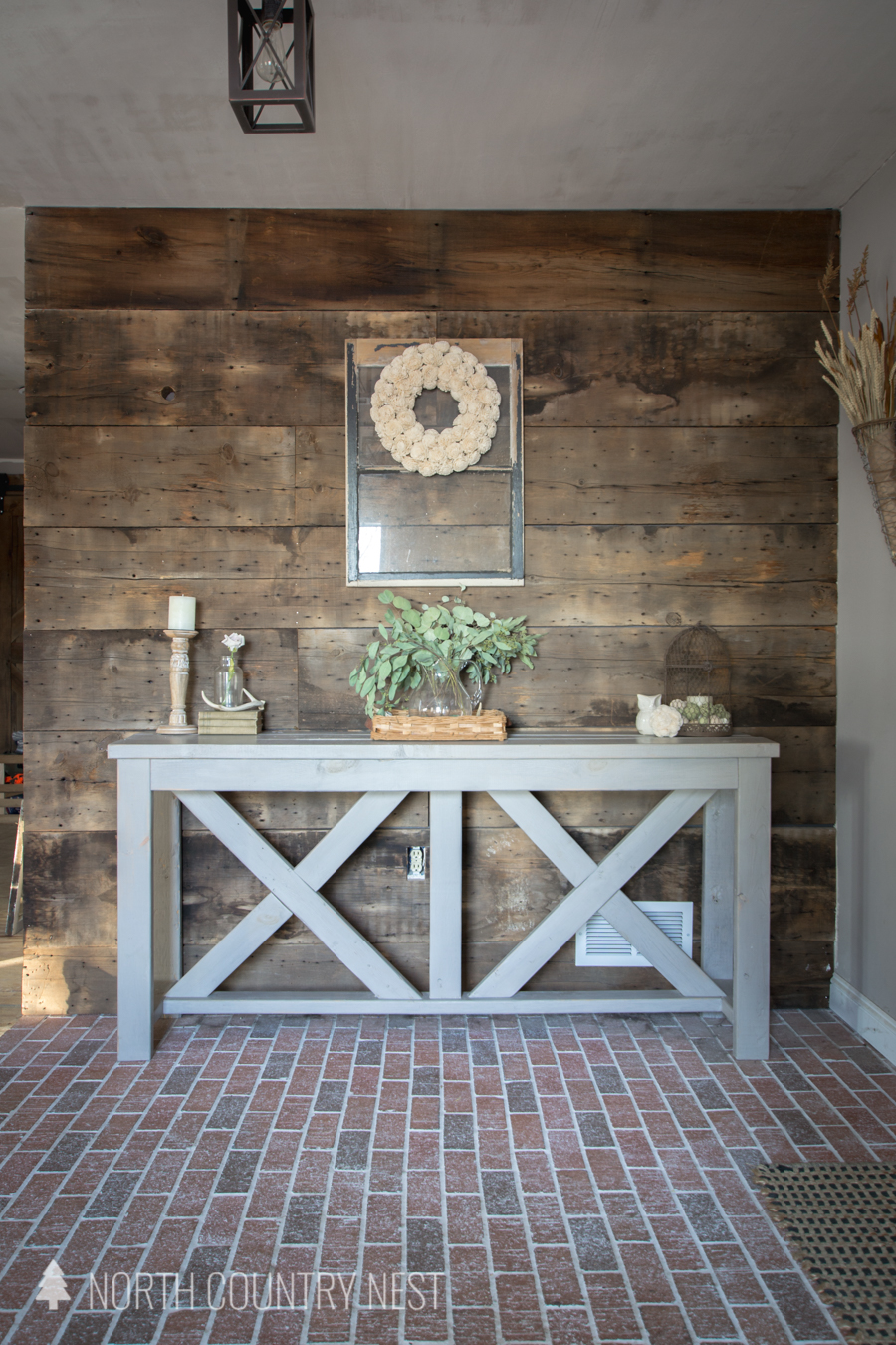 decorated entryway table on brick floor