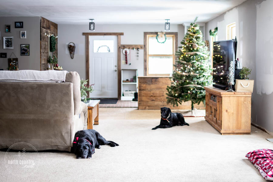living room and entryway decorated for the holidays