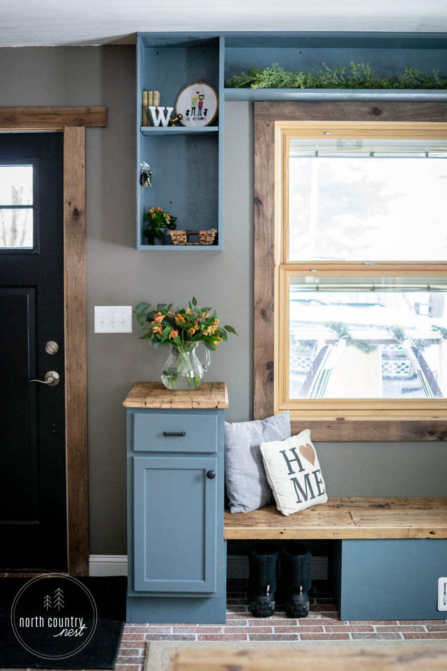 modern rustic entryway with blue built ins and brick floor