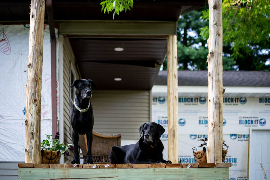 Cedar front porch with two black labs