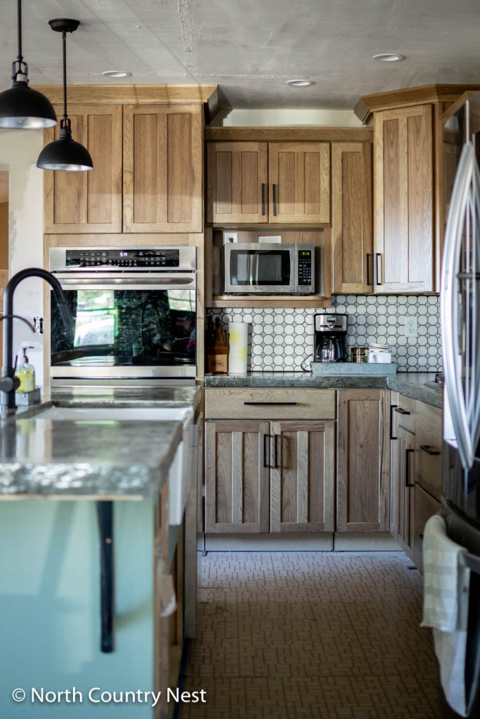 Rustic kitchen renovation with green island and hickory cabinets