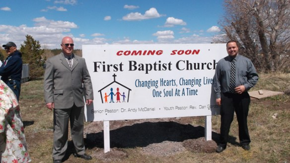 Pastor Andy (Left) and Youth Pastor Dan astride the dedication sign.