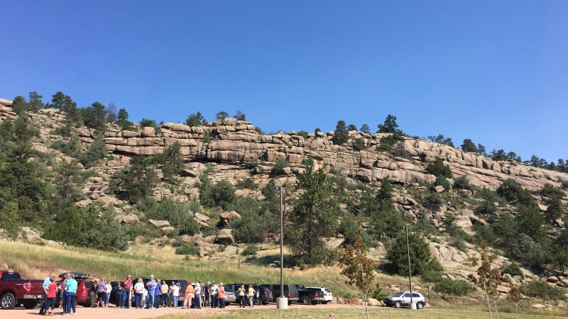 People gather in a gravel parking lot at the base of a large rock outcropping.
