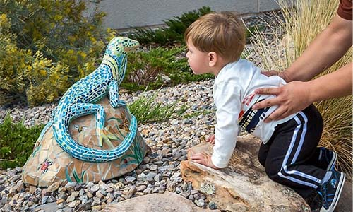 child looking at toy dinosaur in a garden