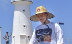 Student in front of lighthouse