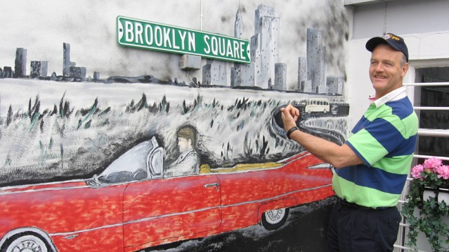 """Svein Skårdal standing by a mural of a red convertible under a """"Brooklyn Square"""" street sign in Vanse, Norway."""
