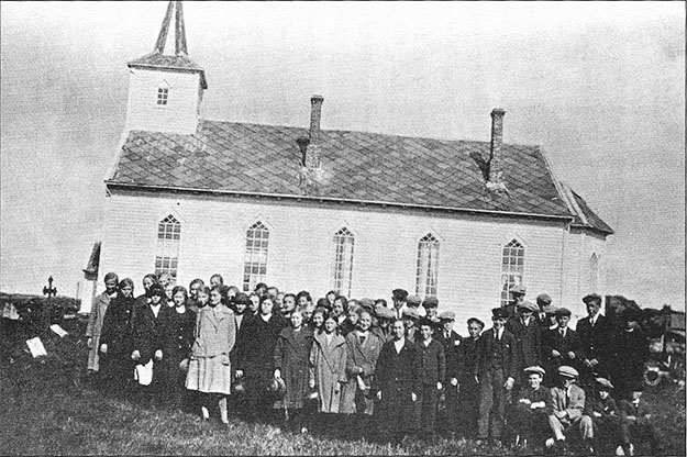 Photo courtesy of Jon Lind In 1901, four cast iron stoves were added to the new church, two on each side, each with its own chimney.  Pictured here is the confirmation class of 1925, standing on the site of the old church.  The chimneys have been since removed.