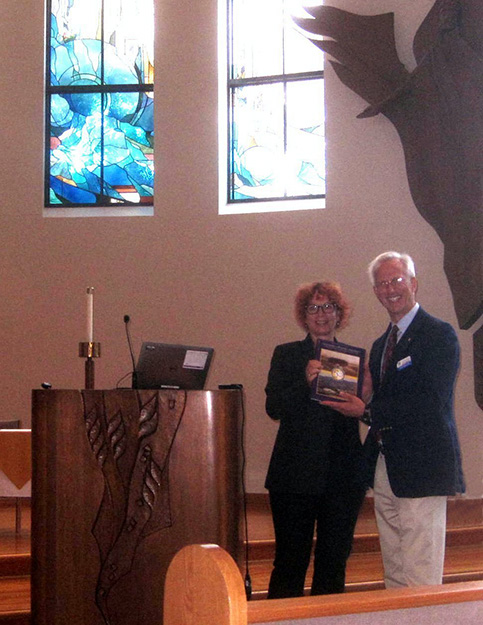 Photo: Ernst F. Tonsing  Seminar chair Knut Oxnevad presents Hilde Skorpen, Royal Norwegian Consul General, San Francisco, a copy of a 50-year history of CLU.  The setting was the campus Samuelson Chapel.