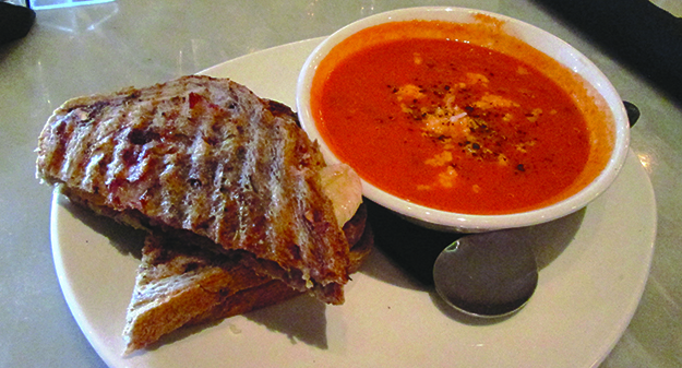 A Gjetost and Banana Grilled Cheese Sandwich and a bowl of tomato soup from Cheesetique