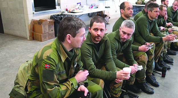 Photo: Aaron Hagström Lt. Eric Nagel (second from left) and other Norwegians wait for the briefing to begin.