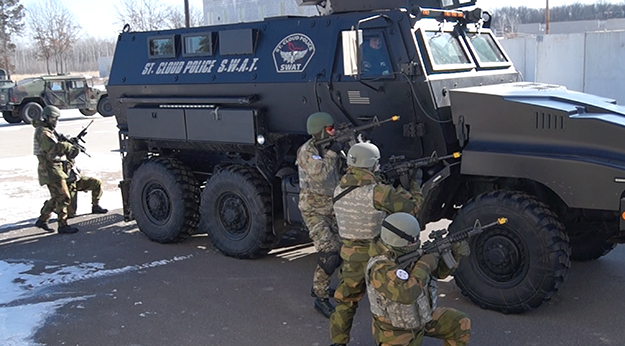Photo: Aaron Hagström  Norwegians look for snipers, using a St. Cloud Police S.W.A.T. vehicle for cover.