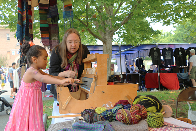 Photo: Solveig Lee A child learns about weaving on a loom.