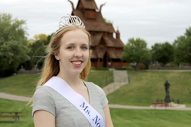 "Photo: Leann Mellum Jane Peterson, 2015's Ms. Norsk Høstfest, in front of the stave church at Minot's Scandinavian Heritage Association. The impressive high school senior is a survivor of bone cancer and a beekeeper who bottles and sells ""Buzz Off Honey,"" and plans to become a nurse practitioner."