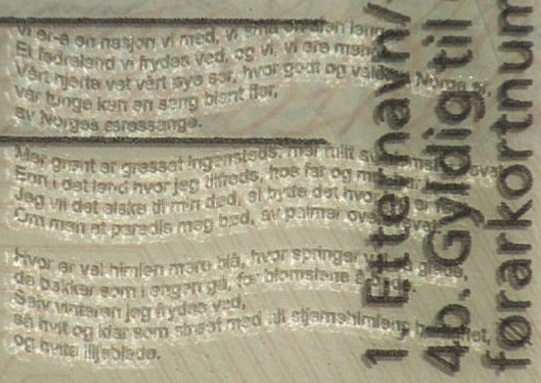 Photo: Norwegian Public Roads Administration Magnified view of first three stanzas of song poem embossed in lower right corner on back of driver's license.